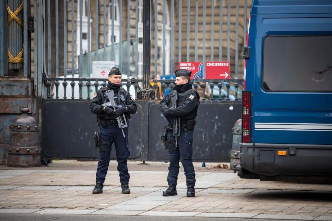 Two French police officers stand guard, holding assault rifles