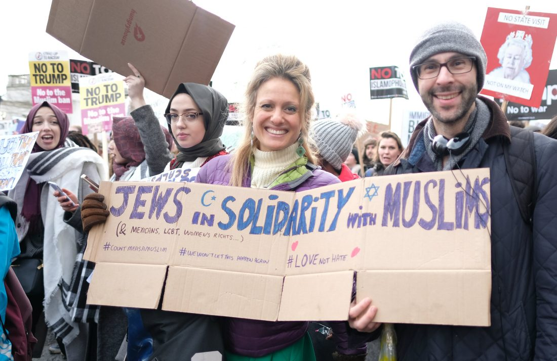 "Woman holding a sign that says ""Jews in solidarity with Muslims"""