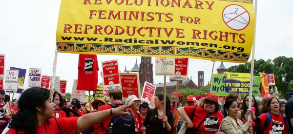 "Members of Radical Women holding a banner that says ""Revolutionary Feminists for Reproductive Rights"""