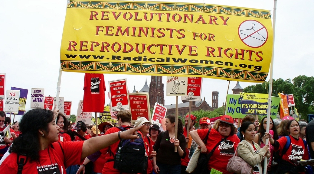 Members of Radical Women holding a banner that says
