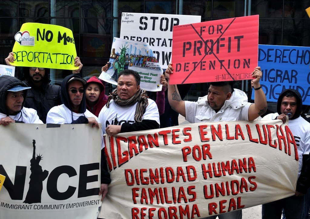 Protestors holding signs against immigrant detention