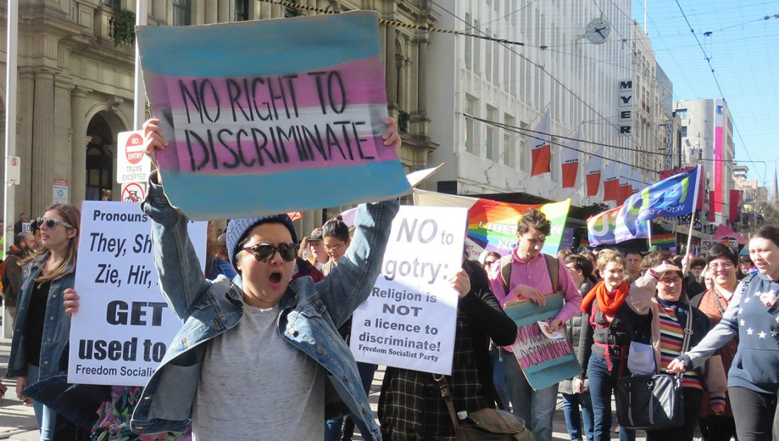 "A woman at a rally holds a sign saying ""No right to discriminate."""