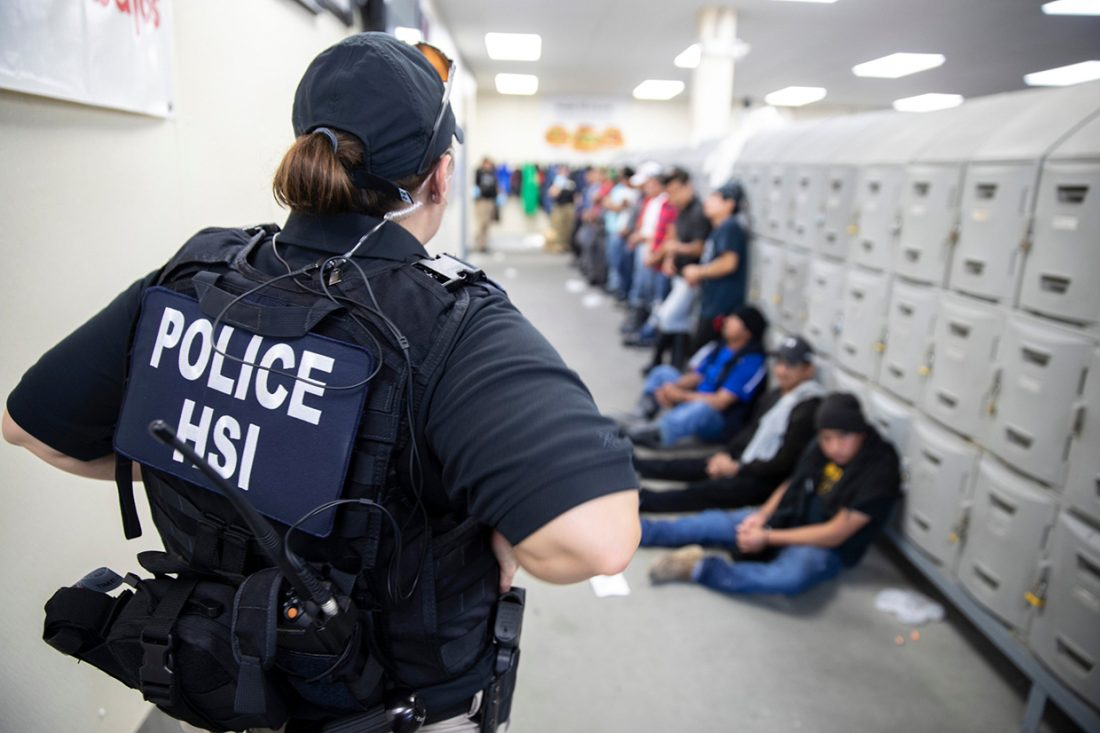 """A uniformed woman with """"POLICE/HSI printed on her back faces the background where a long line of people are waiting."""