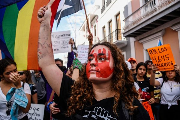 """Foreground: a woman with red handprints painted on her face, fist raised. Background: green, yellow, orange and red striped flag; people holding signs, including one that reads """"POR LOS 4,645 MUERTOS."""""""