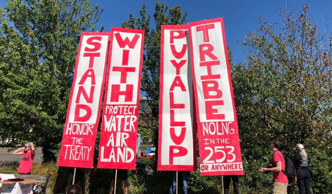 Four vertical banners. The large words are STAND WITH PUYALLUP TRIBE. Smaller words include
