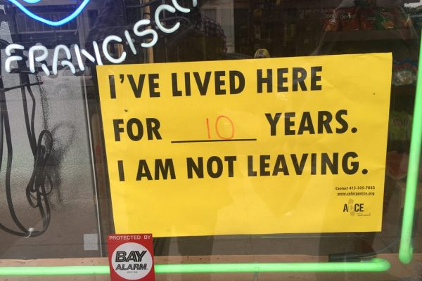 "Partial view of a shop window. A yellow sign with black print that reads ""I've lived here for ____ years. I am not leaving."" The blank space has ""10"" written in red. In upper left, part of a neon sign that reads ""FRANCISCO."""