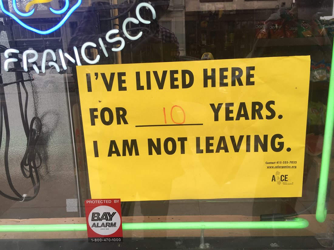 """Partial view of a shop window. A yellow sign with black print that reads """"I've lived here for ____ years. I am not leaving."""" The blank space has """"10"""" written in red. In upper left, part of a neon sign that reads """"FRANCISCO."""""""
