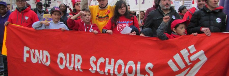"""Protestors holding a banner that says """"Fund Our Schools"""""""