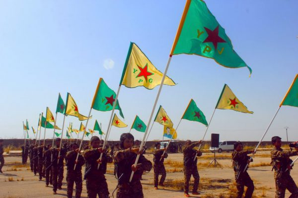 Kurdish YPG and YPJ fighters holding flags