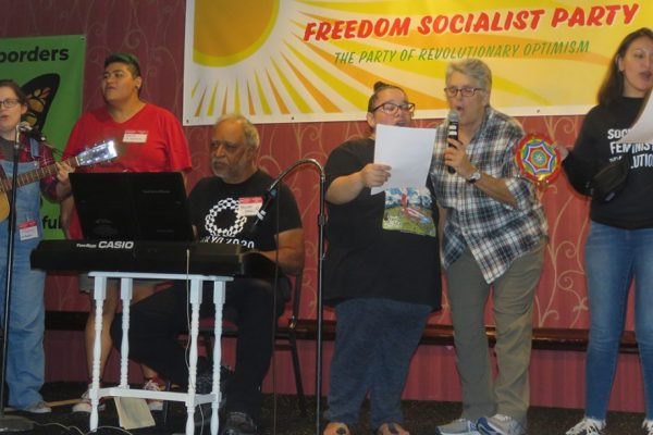 "Six people singing — one playing the guitar, one playing keyboards, and one playing tambourine — perform in front of a banner reading ""Freedom Socialist Party — The party of revolutionary optimism."""