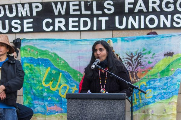 "Kshama Sawant speaking at a podium underneath a banner that reads ""DUMP WELLS FARGO, USE CREDIT UNIONS"""