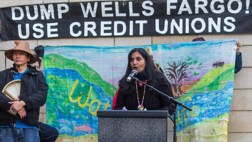 """Kshama Sawant speaking at a podium underneath a banner that reads """"DUMP WELLS FARGO, USE CREDIT UNIONS"""""""