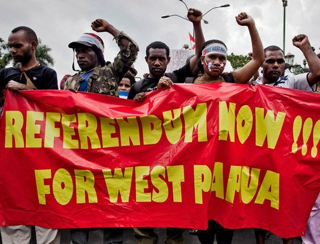 "Papuans holding a banner that reads: ""Referendum Now! For West Papua"""