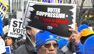 "Man holding a sign that says: ""Voter Suppression = 1% trying to silence the 99%"""