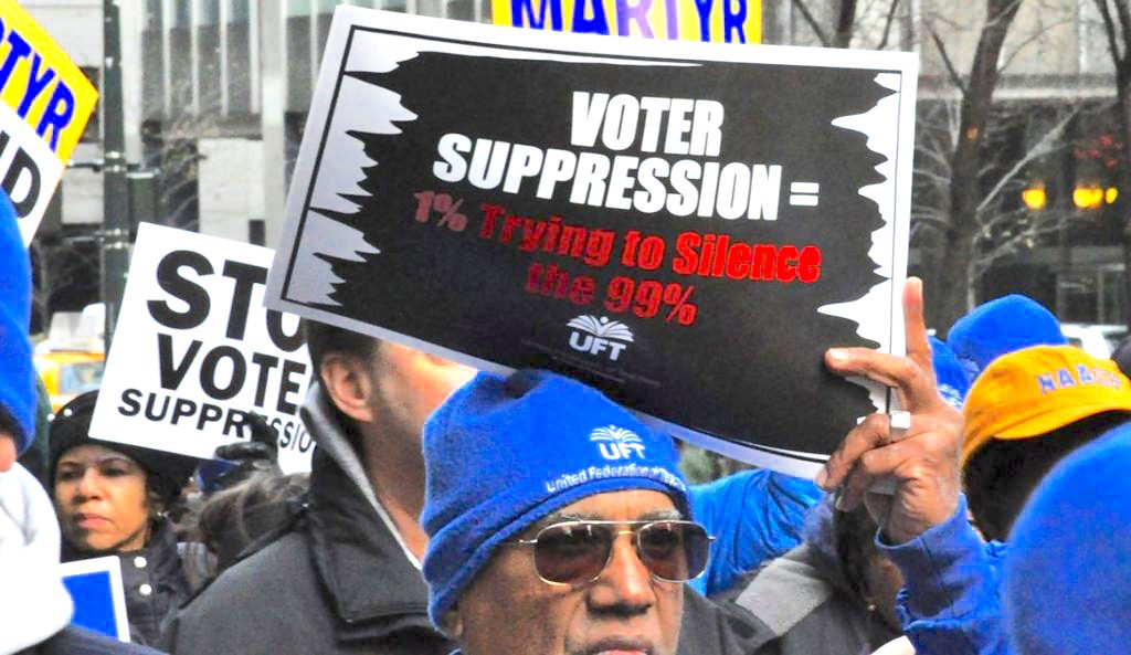 """Man holding a sign that says: """"Voter Suppression = 1% trying to silence the 99%"""""""
