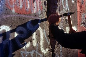 A man chips off part of the Berlin Wall, which is covered with graffiti.