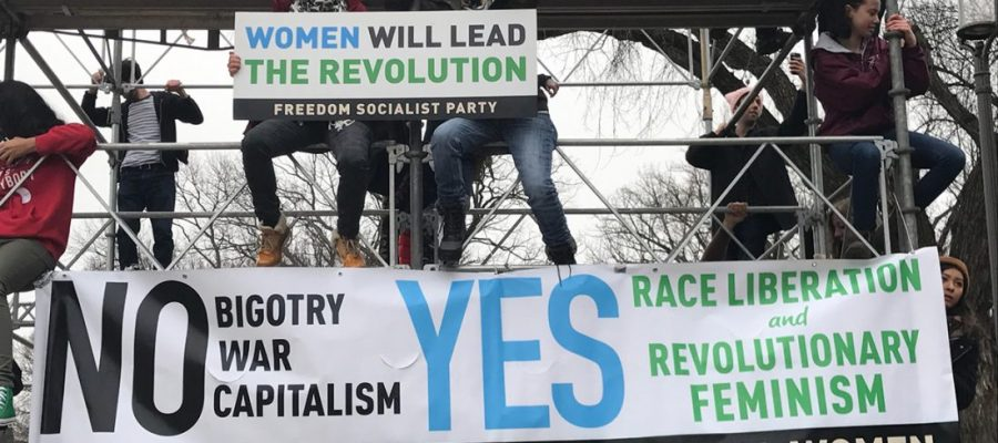 "People on scaffolding hold a sign: ""Wlomen will lead the revolution"" and a banner: ""NO bigotry, war, capitalism; YES race liberation and revolutionary feminism / Freedom Socialist Party / Radical Women"