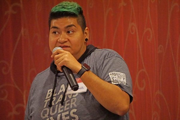 A woman speaks at a microphone. She has green-dyed hair and a shirt reading Black Trans Queer.