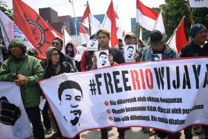 "Indonesian protestors hold a banner that says ""Free Rio Wijaya"""