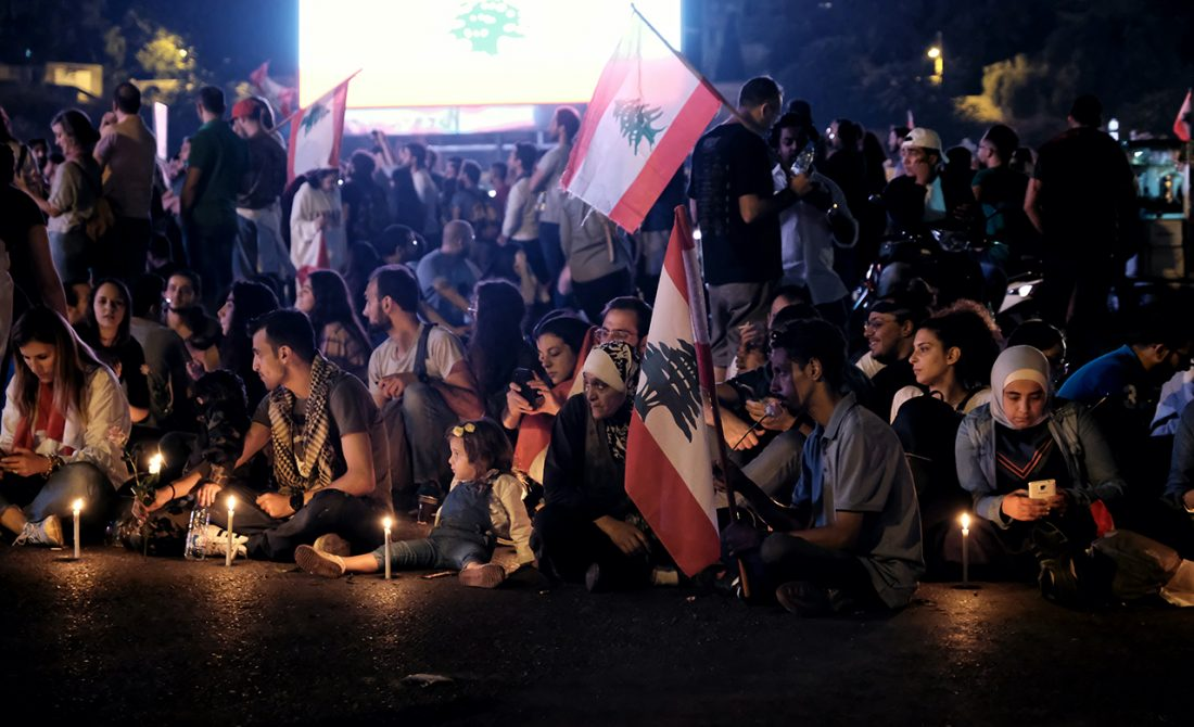 In twilight, a crowd of young and old sit holding flags and cellphones.