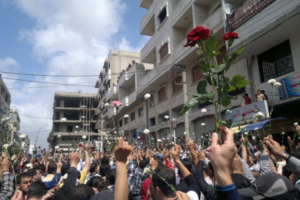 A street view from the back of a crowd, many holding white flowers, one person holding up a red rose.