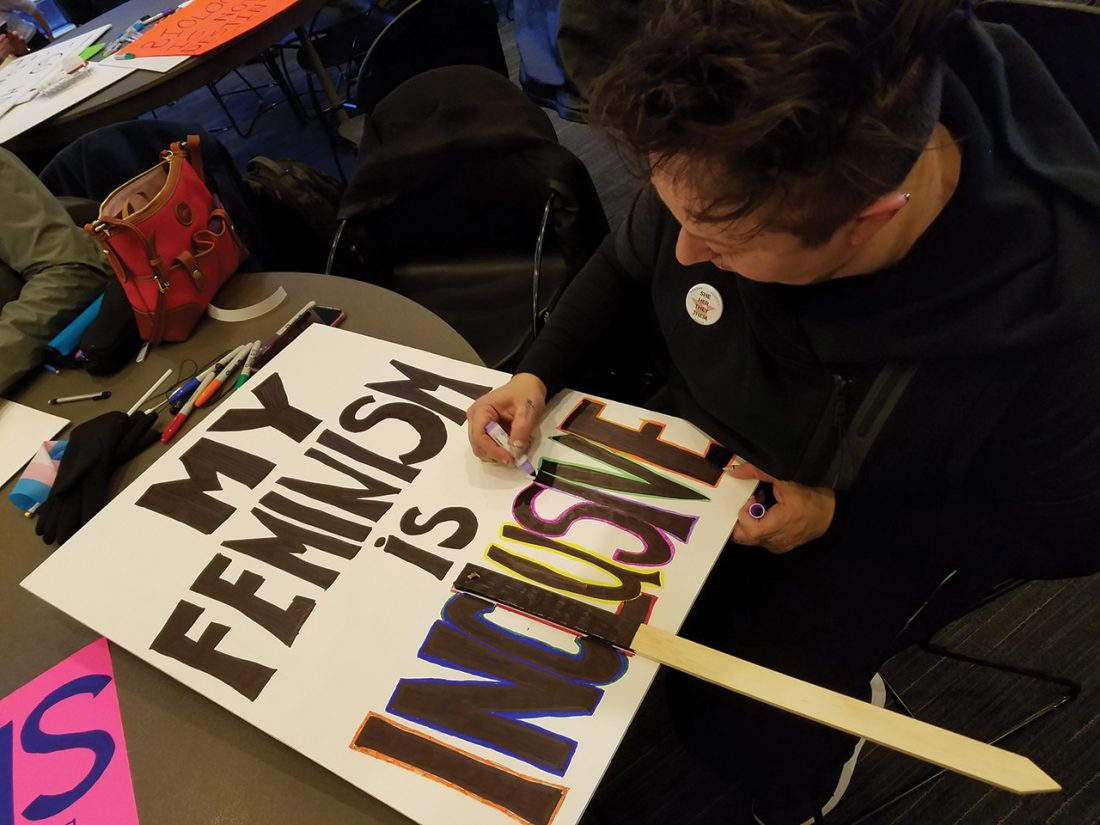 """A person completes a protest sign reading """"My feminism is inclusive."""""""