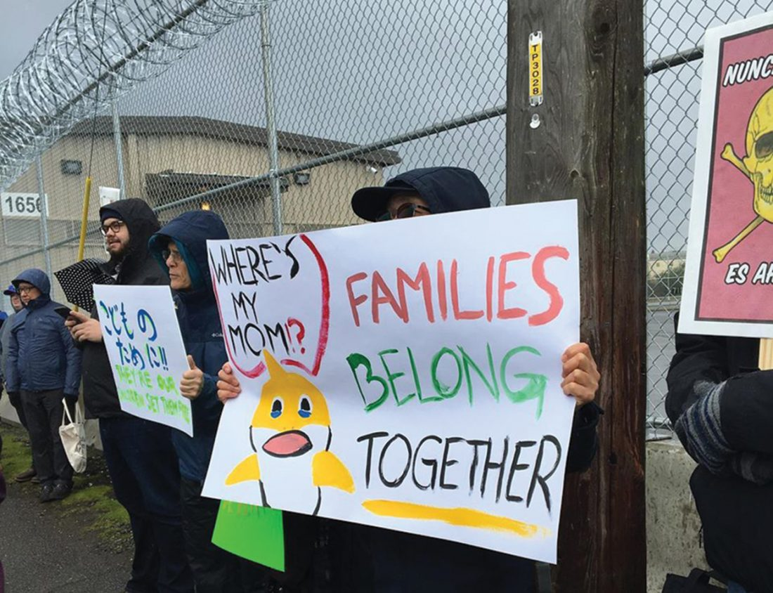 """A person in front of a barbed-wire topped cyclone fence holds a sign that reads: """"Wheres my Mom? Families belong together."""""""
