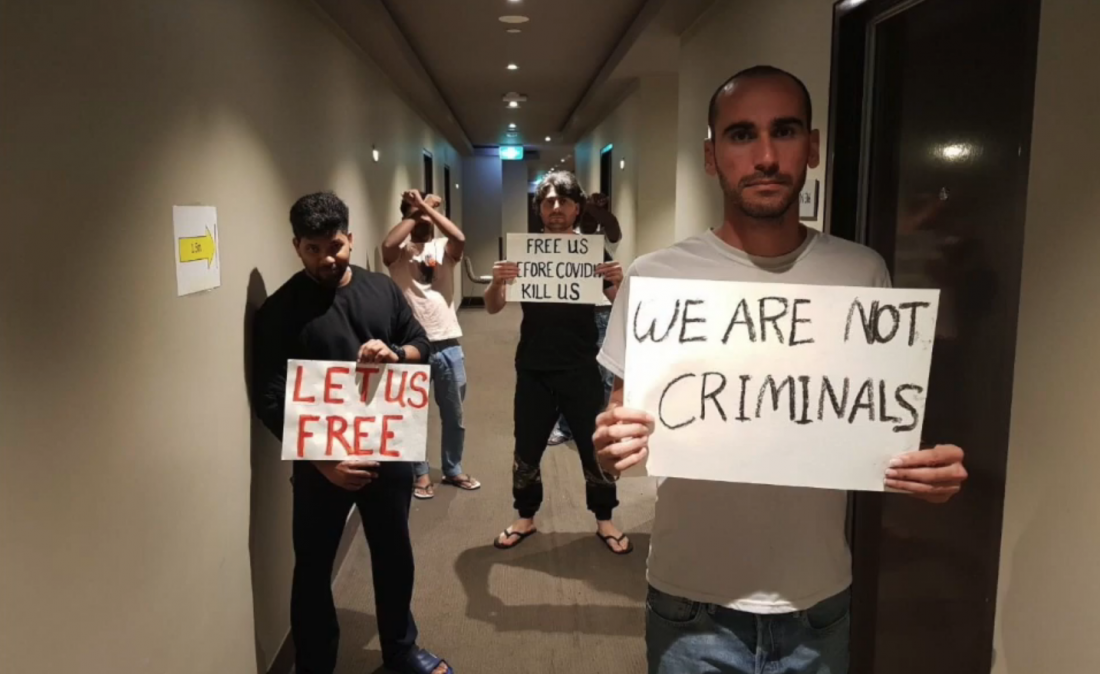 Migrants holding signs asking for their release