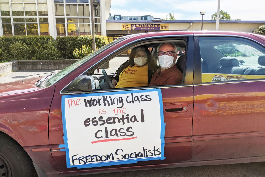 A car protest: two people in facemasks look out the window of a car. The side on the side reads