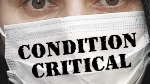 """A woman wears a mask that says """"Condition Critical"""""""