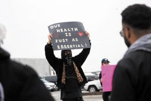 """A man holds up a sign reading """"OUR HEALTH IS JUST AS ESSENTIAL"""""""