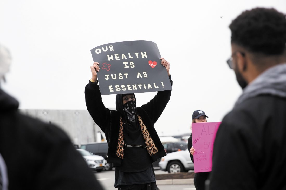 "A man holds up a sign reading ""OUR HEALTH IS JUST AS ESSENTIAL"""
