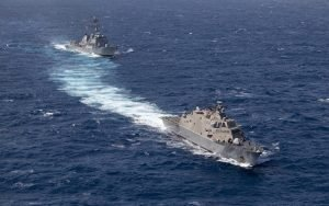 Two military combat ships cruise together.