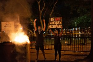 "Two people stand by a burning dumpster, with a row of police in the background. One of the people is holding a sign saying ""By any means necessary."""