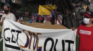 Two men in facemasks hold a banner reading GET SPOG OUT. An OWLS banner can be seen in the background.