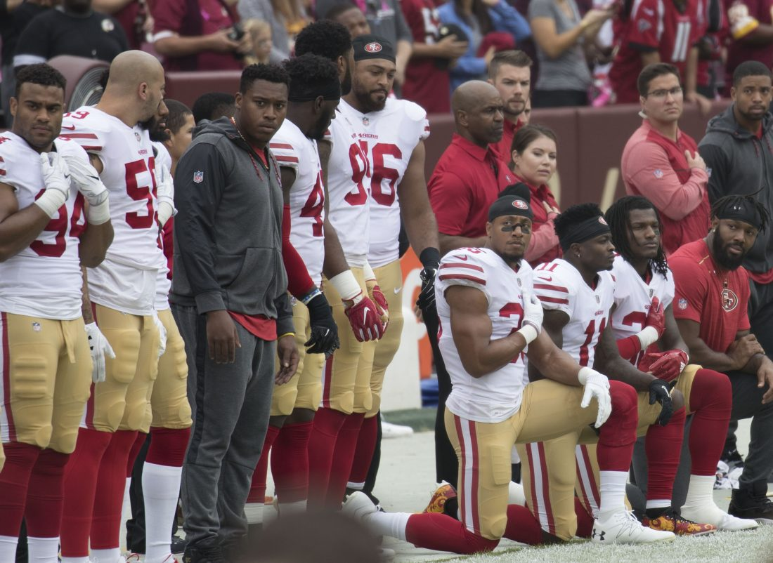 Football players on the sidelines, some standing and some kneeling. They are giving each other questioning looks.