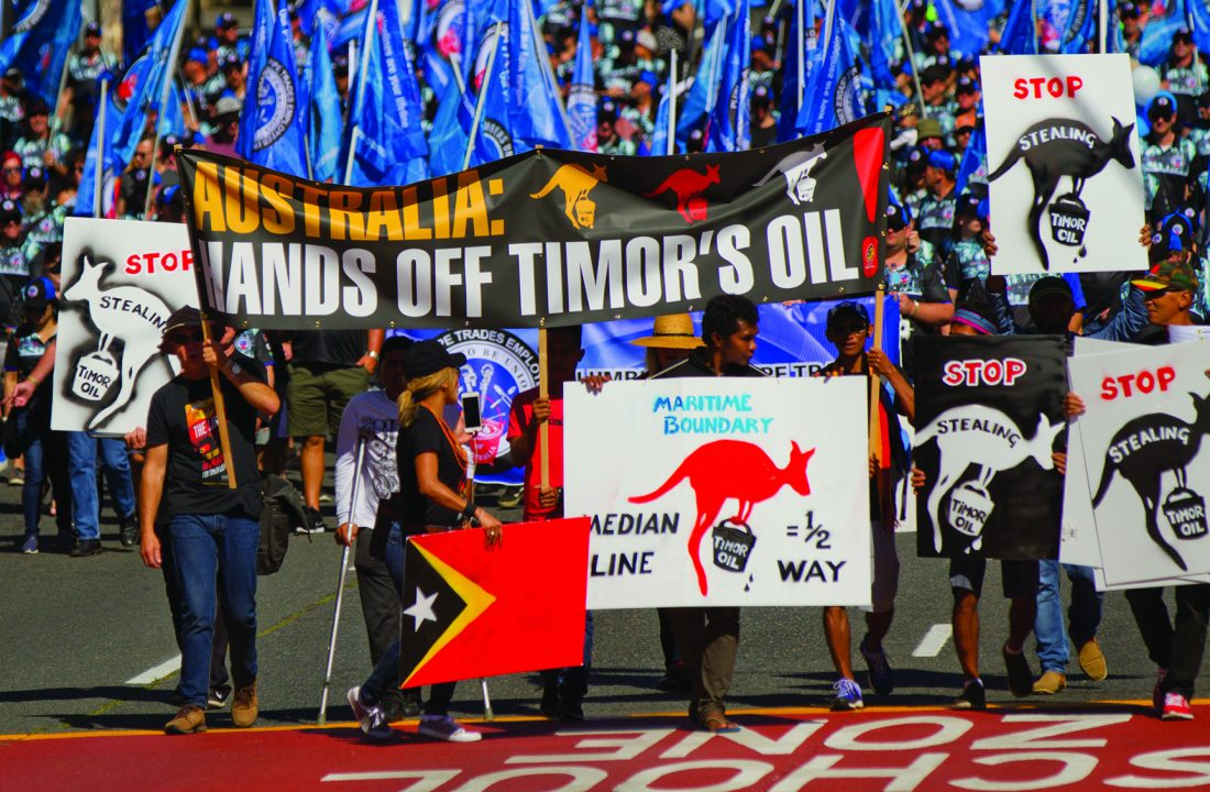 People marching with a large banner that reads AUSTRALIA: HANDS OFF TIMOR OIL. Another sign has a kangaroo graphic and the text MEDIAN LINE = 1/2 WAY. referencing the median line.