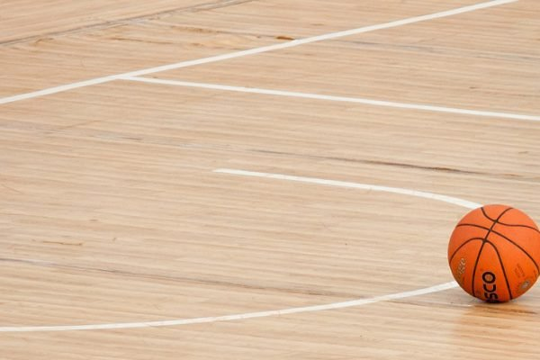 A basketball on an empty court.