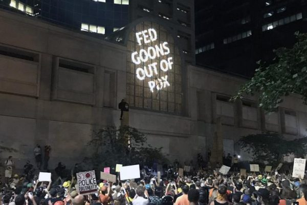 A crowd of protesters in front of a tall dark building, with the words FED GOONS OUT OF PDX projected up on the front.
