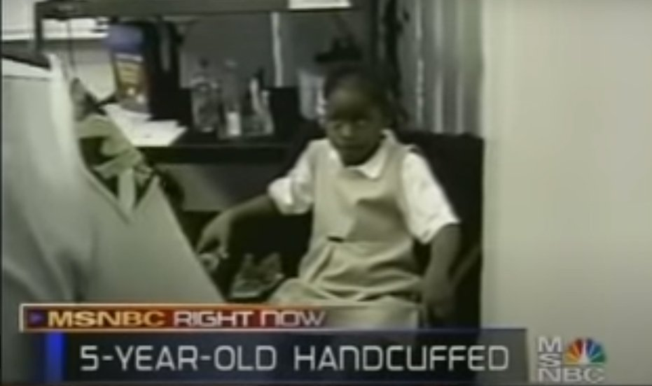 A screenshot of video showing a frightened-looking young Black girl. In the foreground can be seen the shoulder of a uniformed policeman. — MSNBC RIGHT NOW — 5-YEAR-OLD HANDCUFFED