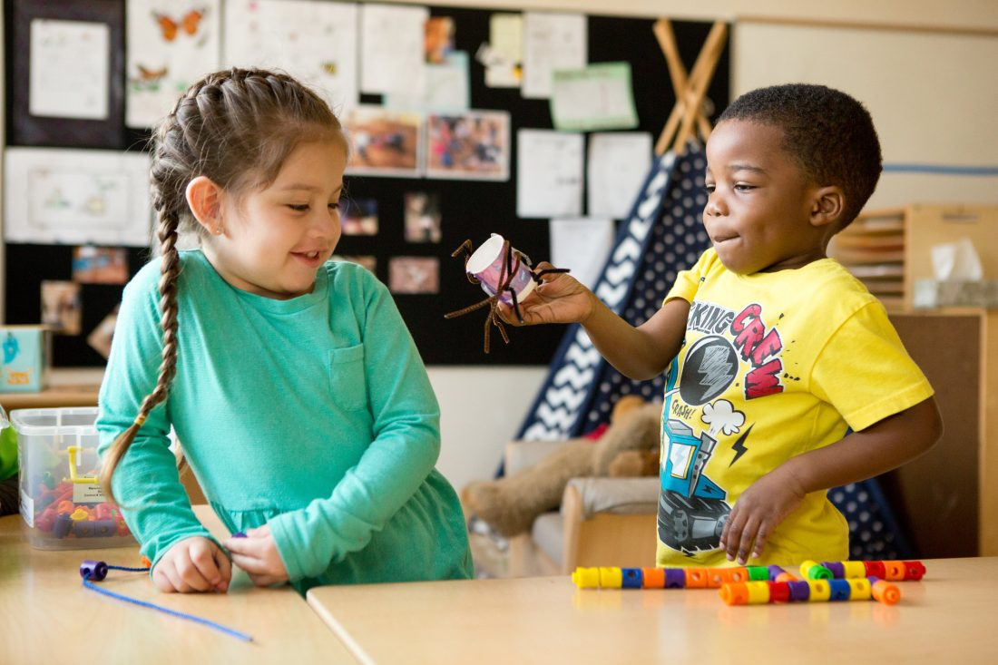 A young boy shows his classmate a spider he made from pipe cleaners and a paper cup.