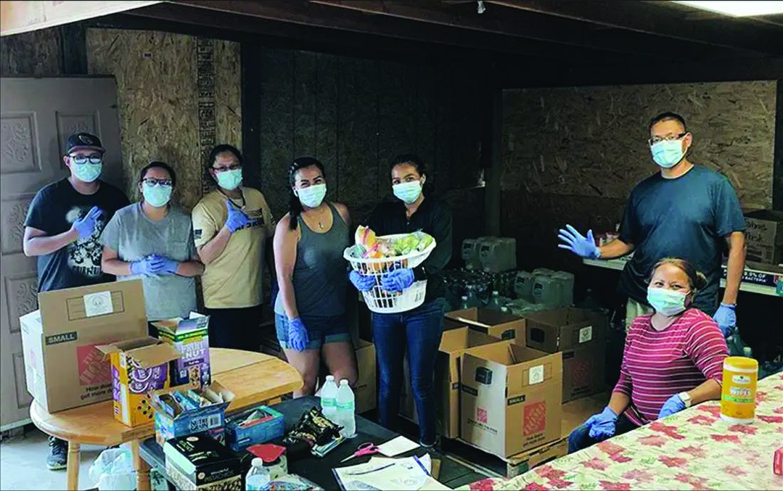 Seven people, all wearing masks and rubber gloves, pose beside boxes of supplies.