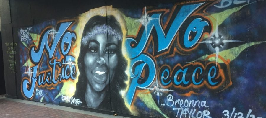 A spray painted mural depicts Breonna Taylor and the words No Justice No peace