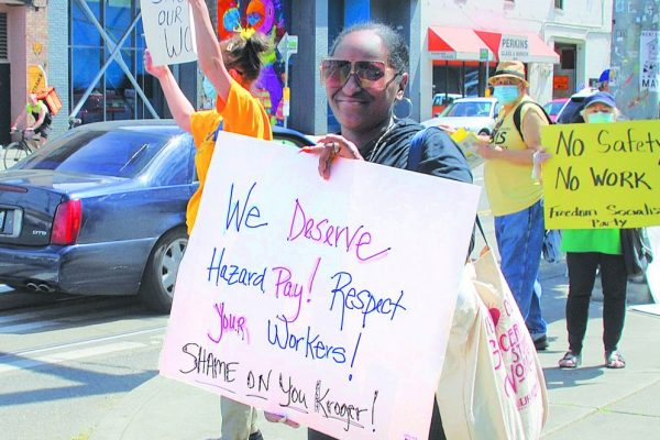 "A woman holds a sign that reads: ""We Deserve Hazard Pay! Respect Your Workers! Shame on you Kroger!"" In the background another sign reads ""No safety No work - Freedom Socialist Party"""