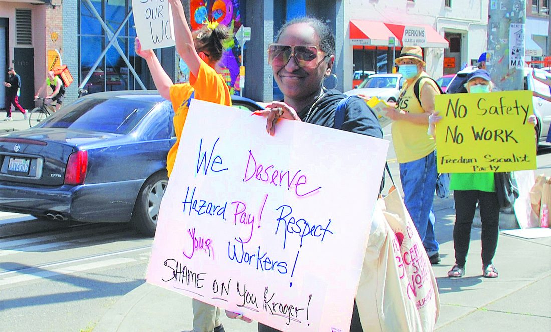 """A woman holds a sign that reads: """"We Deserve Hazard Pay! Respect Your Workers! Shame on you Kroger!"""" In the background another sign reads """"No safety No work - Freedom Socialist Party"""""""