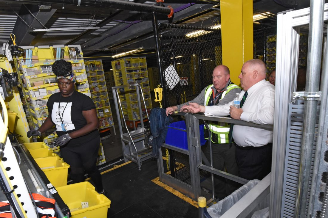 A Black woman works near large yellow bins as two white men look on. One of the men is wearing a white shirt and tie.