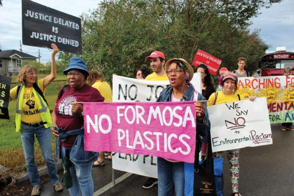 """A group of people with signs march on the side of a paved road. The central sign reads """"NO FORMOSA PLASTICS."""" Other signs read """"Justice delayed is justice denied"""" and """"We say NO to Environmental Racism."""""""
