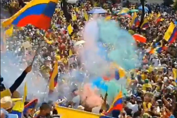 A large crowd waving yellow, blue, and red flags.