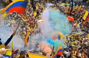 Multicolored smoke drifts over a crowd waving yellow, blue, and red striped flags.