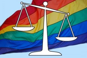 A silhouette of an old-fashioned scale/balance. In the background is a rainbow flag.